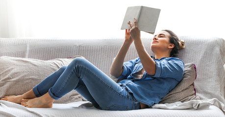 White cozy bed and a beautiful girl, reading a book, concepts of home and comfort