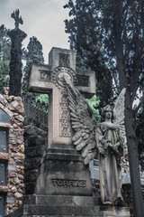 Sculpture of an angel with cross  on a cemetery