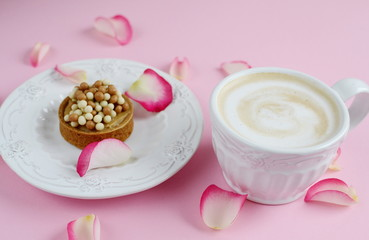 Cup of cappuccino and cake with pink roses on the table