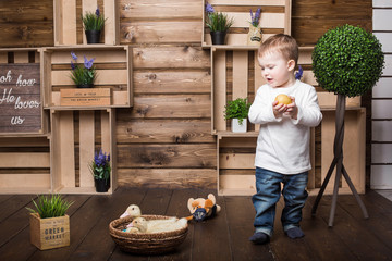 boy playing with a live duck inside a decorated wooden house