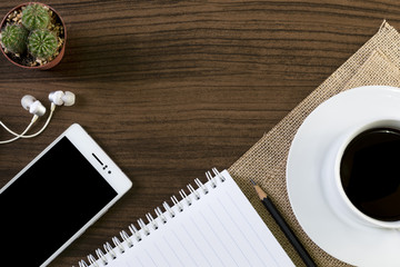 Cup of coffee and smartphone on wooden background