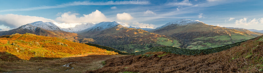 Stunning snowcapped mountains with golden vibrant morning light in the Lake District. Wall mural