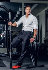 Stylish male holds barbell in a gym club.