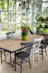 Dining room interior with table, chairs and plants against big windows