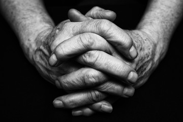 Old hands clasped together. Black and white photography