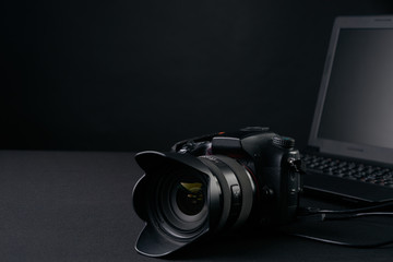 Closeup of professional  photography camera,modern laptop, home illustration & equipments on creative desk . business conceptual