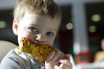 Child eating grilled cob corn
