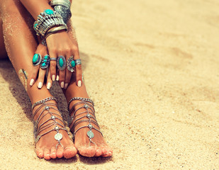Woman  feet and hands In Tropical Beach with sand , body parts  . Tanned girl  foot with silver jewelry,bracelets and rings with turquoise.