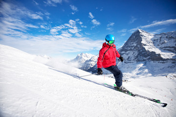 Young attractive caucasian skier on ski slope in famous Jungfrau ski resort in Swiss Alps, Grindelwald, Switzerland