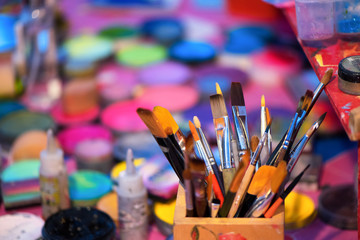 Paintbrushes with a colorful background and shallow depth of field