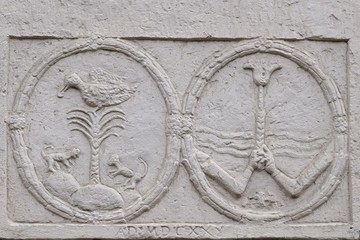 Two round anaglyphs with palm, duck, monkeys and two hands holding a flower on wall of neobaroque-classicistic mansion in Horne Lefantovce, Slovakia