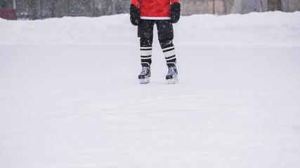 hockey skates standing on ice with hockey stick