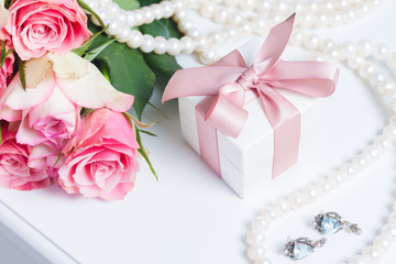 Present box with pink ribbon with jewellery and roses on white table