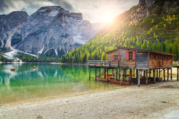 Wooden boathouse and boats on the alpine lake, Dolomites, Italy