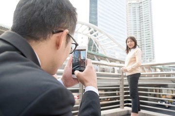 Businessman photographing businesswoman with his mobile phone camera in city. Boyfriend taking picture girlfriend with smartphone outdoor over building background or of urban landscape. Focus on phone