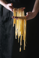 Fresh raw uncooked homemade pasta tagliatelle in man's hands over black apron as background.