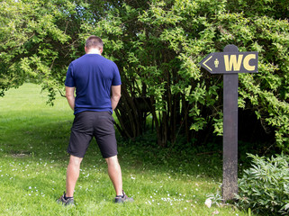 man urine in the countryside beside signs toward the WC. Natural toilet.