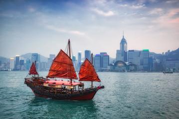 traditional wooden sailboat sailing in Hong Kong harbour at Hong Kong city on background