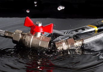 disconnected flexible fittings, ball valve, union and adjustable wrench in water with falling drops and waves, black background