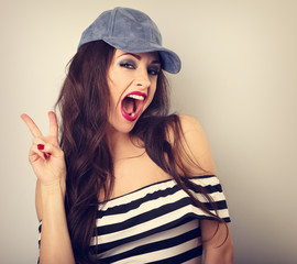 Crazy young female model in blue hat showing rock gesture with wide opened mouth. Bright makeup and red lipstick. Toned vintage closeup portrait