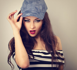 Beautiful sexy young make-up model holding fashion blue cap and posing on blue background with empty copy space. Long hairstyle and red lipstick. Toned closeup portrait