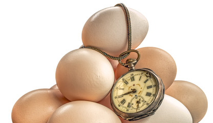 Eggs time - An old pocket watch on a pile of eggs