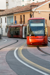 European urban red train rides on the urban rail in Italy, day, daylight, front view, vertical shot, space for text
