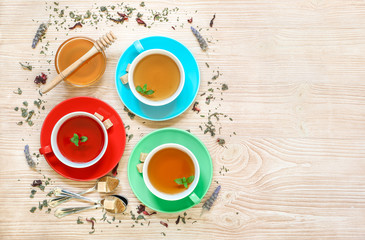 Tea Collection of three different types of tea - mint, hibiscus and herbal tea in cups isolated on wood background.