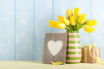 Fresh yellow tulips, gift box and heart shaped frame