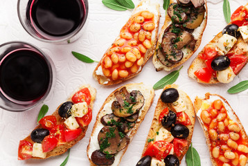Brushetta set for wine. Variety of small sandwiches with caprese salad , white beans on the grill with tomato sauce and fried mushrooms with soft cheese, served with red wine