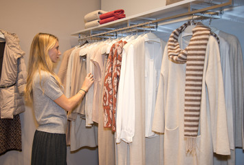 Young woman choosing clothes in clothing store