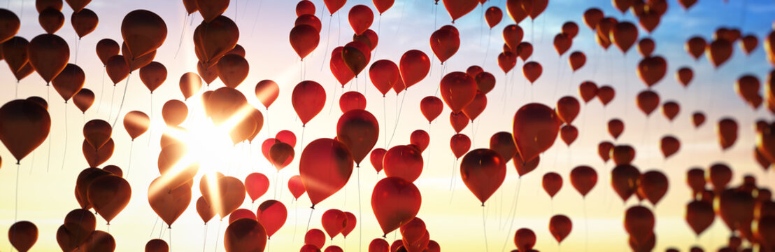 Rote Luftballons im Abendhimmel mit Sonne