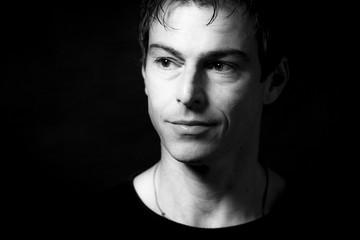 Close up portrait of handsome smiling caucasian man. Black background. Monochrome picture