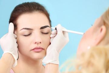 Young beautiful woman making permanent makeup in cosmetology salon