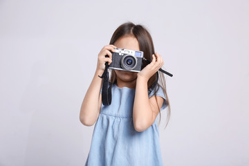 Little girl with vintage camera on light background