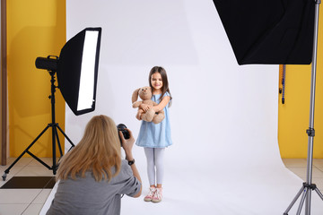 Photographer taking photo of cute little girl with toy bear on light background