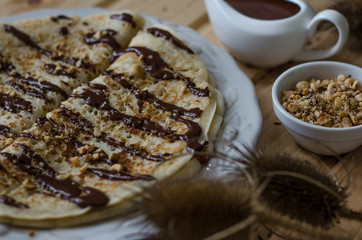 Pancakes with chocolate sauce and nuts for breakfast