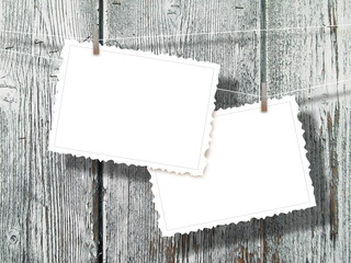 Two blank postcard frames hanged by pegs against gray weathered wooden boards background