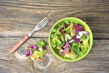 Wall Mural - Fresh mixed green salad in bowl on wooden table close up