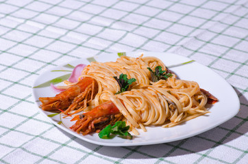 A delicious plate with shrimps, tagliatelle and sauce.