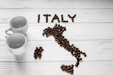 Map of the Italy made of roasted coffee beans laying on white wooden textured background with two coffee cups. Space for text