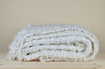 White soft woolen blanket with cozy look on wooden shelf