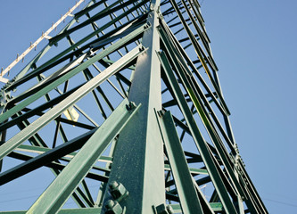 Detail of the electric pylon green with bolts.