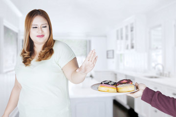Beautiful woman refuses to eat donuts