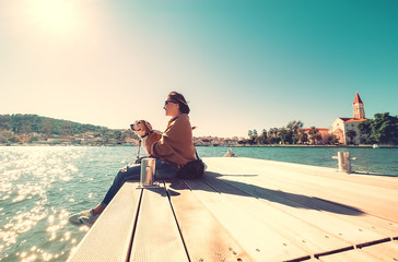 Woman sits with dog on wooden sea pier at sunny windy day