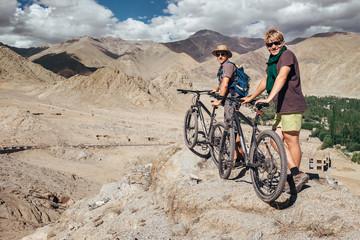 Two tourists with bikes explore Himalaya mountain region