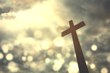 Cross symbol with bright sunlight on sky
