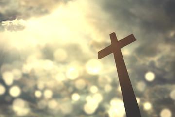 Cross symbol with bright sunlight on sky