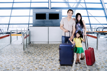 Family with suitcases in the airport terminal