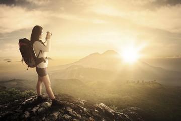 Female photographer takes photos in mountain peak